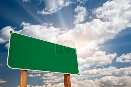Photo for Blank Green Road Sign over Dramatic Blue Sky with Clouds and Sunburst - Ready for your own message and Room For Copy on Clouds. - Royalty Free Image