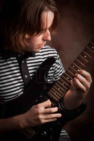 Young Musician Plays His Electric Guitar with Dramatic Lighting.