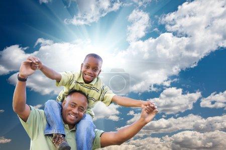 Photo pour Heureux homme afro-américain avec enfant sur ciel bleu, nuages et rayons de soleil . - image libre de droit
