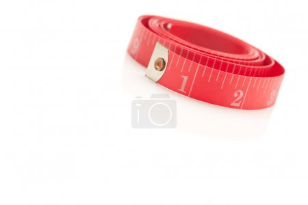 Coiled Red Measuring Tape on White