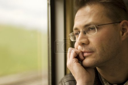 Photo for Thinking man looking out of window, in the train - Royalty Free Image
