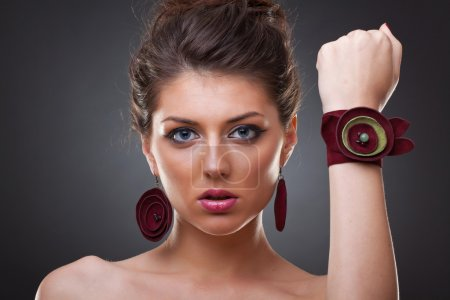 Photo for Close-up portrait of a young woman wearing burgundy leather earrings and bracelet - Royalty Free Image