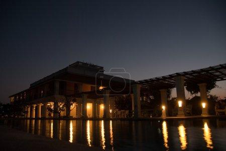 Photo pour Une belle maison avec des lumières reflétant dans la piscine pendant la nuit - image libre de droit