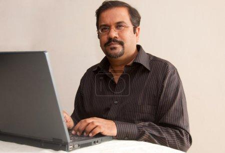 Photo pour Un homme indien sur son ordinateur portable - image libre de droit