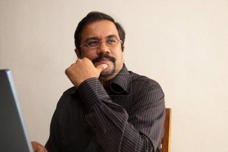 Photo pour Un homme indien pense tout en restant assis en face de son ordinateur portable - image libre de droit