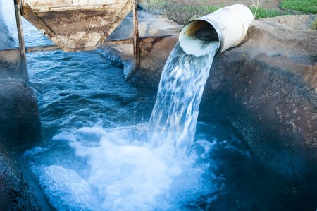 Photo pour Eau s'écoulant d'un tuyau dans un canal d'irrigation - image libre de droit