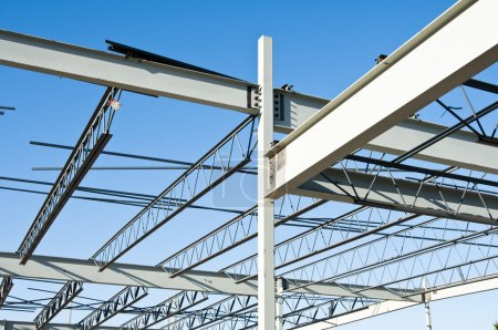 Photo for The structural steel structure of a new commercial building against a clear blue sky in the background - Royalty Free Image