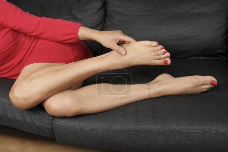 Photo for Beautiful woman legs massaging aching feet lying - Royalty Free Image