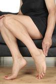 Woman legs massaging aching feet
