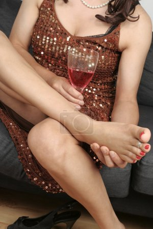 Woman legs massaging feet with drink