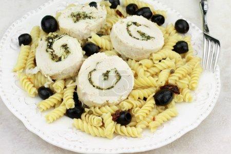Photo pour Roulade de poulet cuit à la vapeur farci de feuilles de basilic haché frais et noix. servi sur pâtes rotini italienne aux tomates séchées et aux olives. - image libre de droit