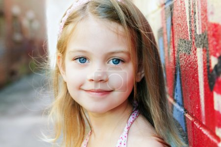 Photo for Little girl in an urban setting smiles at the camera. - Royalty Free Image