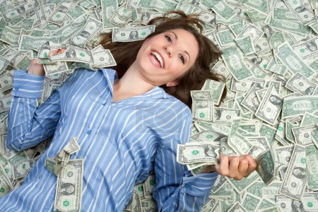 Photo for Beautiful woman laying in money - Royalty Free Image