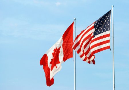Photo pour Drapeau américain canadien sur un ciel bleu - image libre de droit