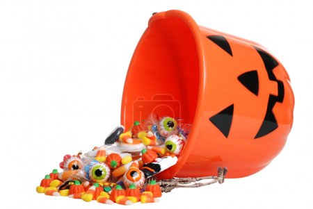 Isolated child halloween pumpkin bucket spilling candy on white background