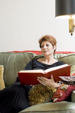 Foto de Una hermosa mujer madura es relajante en el sofá con un libro. - Imagen libre de derechos