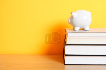 Photo for A piggy bank on top of a stack of books, good for saving for college theme - Royalty Free Image