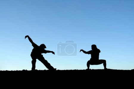 Photo for Two persons practicing martial arts on top of a mountain (in silhouette) - Royalty Free Image