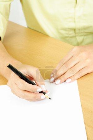 Photo pour Une femme d'affaires écrit sur un morceau de papier blanc - image libre de droit