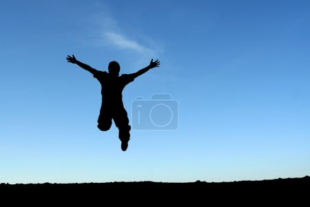 Foto de Un hombre feliz saltando en el aire, en silueta - Imagen libre de derechos