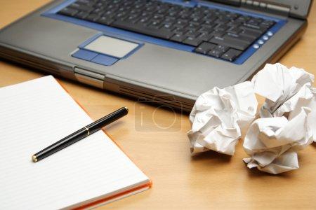 Foto de Una computadora portátil y una libreta con papel arrugado, puede utilizarse como concepto de planes de negocio - Imagen libre de derechos
