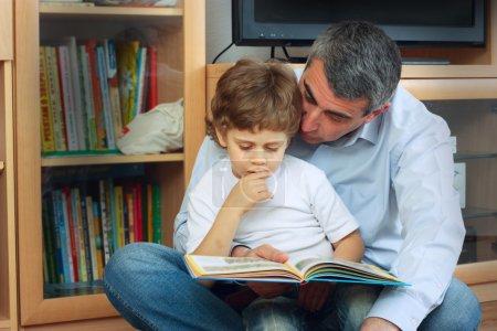Photo pour Homme et petit garçon assis sur le sol dans le salon et la lecture livre - image libre de droit