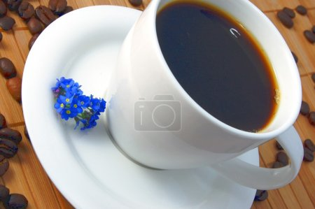 Photo for A white cup between brown coffee beans - Royalty Free Image