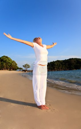 Photo for Young Beautiful woman doing relaxation exercises on sand beach - Royalty Free Image