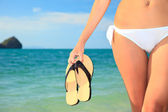 Woman holding a pair of flip flops