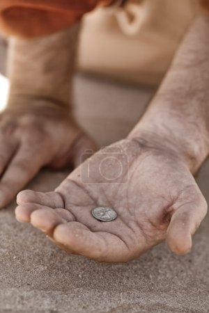 Photo pour Main tenant une pièce unique - mendiant, démuni, donation, charité, bon Samaritain, etc., agrandi avec faible profondeur DDL. - image libre de droit