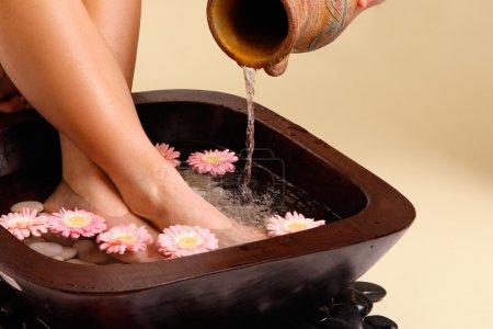Photo pour Eau, verser dans un pot en terre cuite dans un bain de pieds aromatiques luxueux - image libre de droit