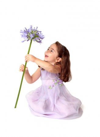 Little girl spins large purple flower