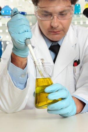 Scientist in laboratory using pipette