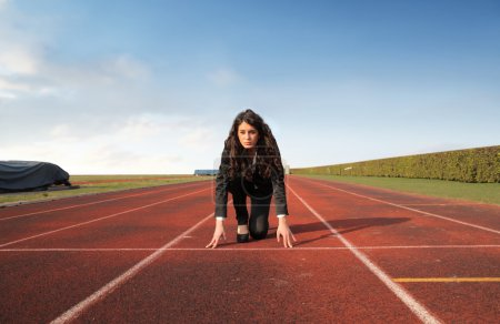 Photo for Young businesswoman kneeling on the starting grid of a running track - Royalty Free Image