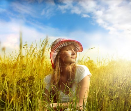 Photo for Beautiful woman sitting on a wheatfield - Royalty Free Image
