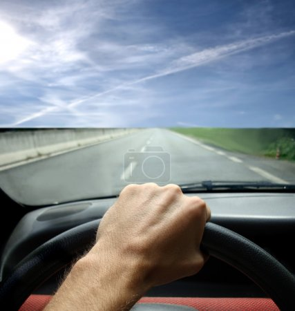 Photo for Detail of a man's hand holding the steering wheel of a car and driving on a highway - Royalty Free Image