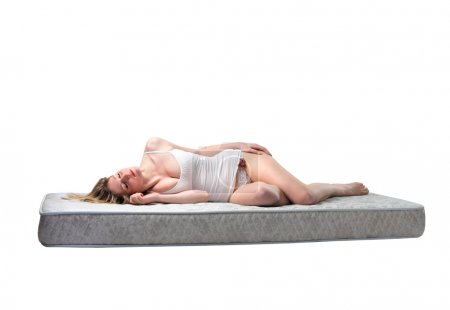 Young woman sleeping on a mattress...