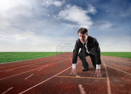 Photo for Businessman kneeling on the starting grid of a running track - Royalty Free Image