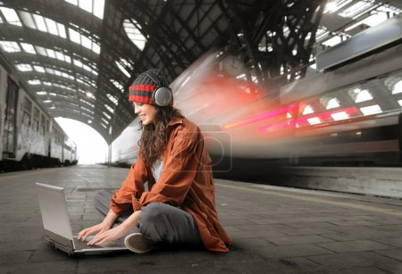 Photo for Young woman sitting on the platform of a train station and using a laptop - Royalty Free Image