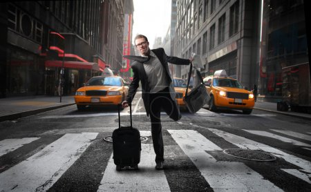 Photo for Businessman carrying a suitcase running on a city street - Royalty Free Image
