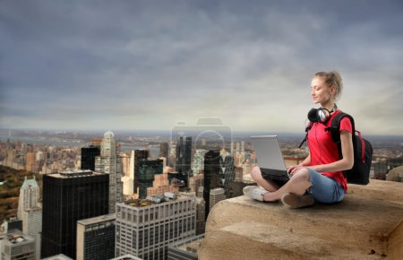 Photo for Young woman sitting on the top of a skyscraper and using a laptop - Royalty Free Image