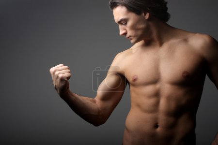 Photo for Man looking at his biceps - Royalty Free Image