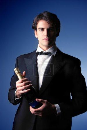 Photo pour Portrait d'un bel homme élégant avec une bouteille de champagne - image libre de droit