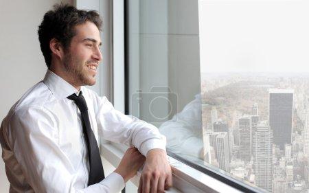 Photo pour Sourire d'homme d'affaires à la recherche d'une fenêtre - image libre de droit
