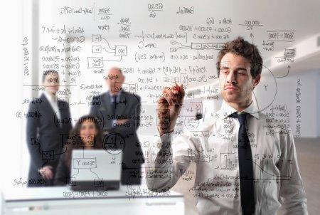Photo pour Homme d'affaires écrivant quelques schémas avec le groupe d'affaires sur le fond - image libre de droit