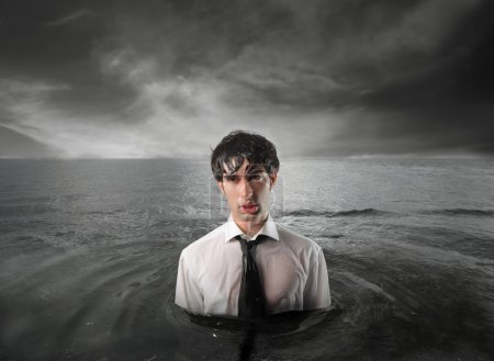 Photo for Wet businessman inthe water with stormy sky above him - Royalty Free Image