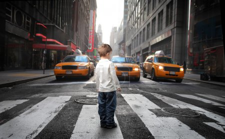 Photo for Child standing on a city street full of cars - Royalty Free Image