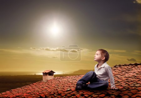 Photo for Child sitting on a rooftop and looking at the sun - Royalty Free Image