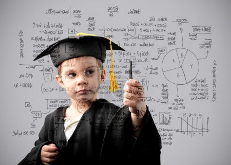 Photo for Child in graduate uniform writing some formulas - Royalty Free Image