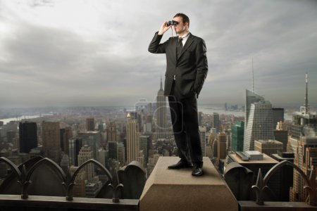 Photo for Businessman using binoculars on the rooftop of a skyscraper - Royalty Free Image